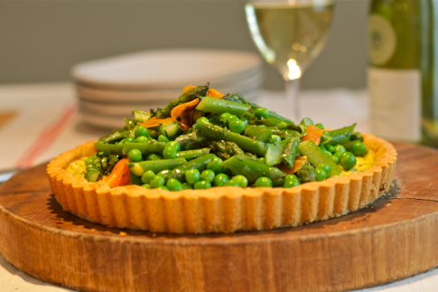 Herbed ricotta cheese tart topped with spring vegetables and an almond ...